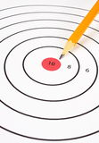Shooting Target and Yellow Pencil. Close up of a shooting target with a yellow pencil pointing at the red bullseye Royalty Free Stock Photo