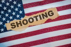 The word Shooting on the American Flag in torn paper Stock Photos