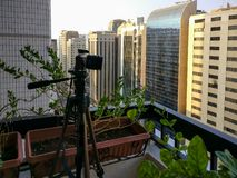 Shooting a time lapse of the sunset in a balcony in the city - camera and tripod royalty free stock images