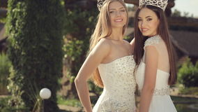 Shooting of two gorgeous girls in wedding dresses. And crowns with precious stones for the fashion magazine in the park outdoors stock video