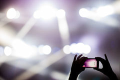 Shooting video clip with mobile phone during a concert. Recording video clip with smartphone during a concert royalty free stock photos