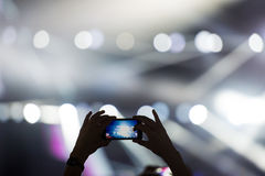 Shooting video clip with mobile phone during a concert Stock Photos