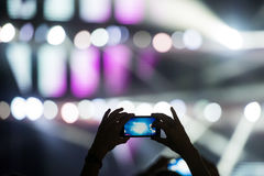 Shooting video clip with mobile phone during a concert Royalty Free Stock Images