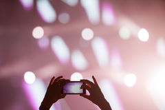 Shooting video clip with mobile phone during a concert Royalty Free Stock Photo