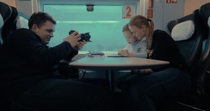 Shooting video of mom and child using pad during train ride. Man stocker taking video of mother and son traveling in train and passing the time with digital stock footage