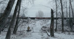 Shooting video of passing freight train. Stocker with camera on tripod taking video of cargo train running in countryside. Winter scene stock video footage