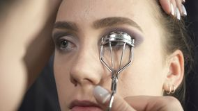 Shooting of visagist using eyelash tongs. Video of visagist using eyelash curler in beauty studio stock video