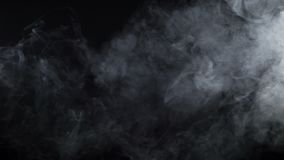 Shooting of white cigarette mist on black background. Video of cloudy smoke of electronic cigarette on black background stock video footage