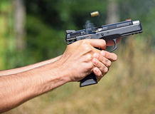 Shooting wigh a pistol. At the shooting contest Royalty Free Stock Photo