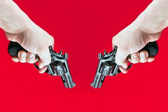 Shoots out two revolvers. On a red background Royalty Free Stock Image