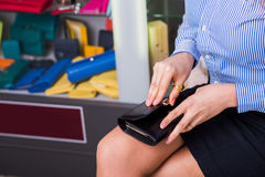 Shop accessories. Business buyer opens wallet,. Beautiful female hand closeup. behind Showcases with accessories Stock Photo