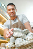 Shop assistant balancing stack cheeses Stock Images