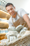 Shop assistant with basket cheeses Stock Photo