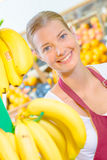 Shop assistant behind stand bananas. Shop assistant behind stand of bananas Stock Photography