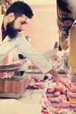 Shop assistant carving meat. American shop assistant carving meat to sell in butcher's shop Royalty Free Stock Images