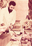 Shop assistant carving meat. Arab shop assistant carving meat to sell in butcher's shop Royalty Free Stock Photo