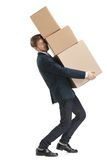 Shop assistant delivers the heavy parcel of three boxes. Shop assistant carries the parcel consisting of three boxes, isolated, white background Royalty Free Stock Images