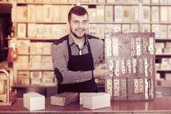 Shop assistant displaying door and furniture knobs. Young male shop assistant displaying door and furniture knobs in houseware shop Royalty Free Stock Photo