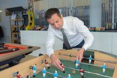 Shop assistant fixing football table. Shop assistant fixing a football table Stock Photo