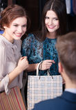 Shop assistant gives a piece of advice to clients. Shop assistant gives a piece of advice to beautiful clients Royalty Free Stock Photos