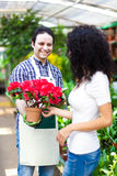 Shop assistant giving a flower pot to a customer Stock Images