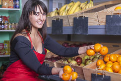 Shop assistant at the greengrocer. Friendly shop assistant at the corner shop puts some mandarine oranges into a wooden box at the fruit shelf royalty free stock images