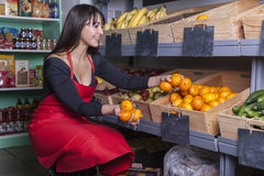Shop assistant at the greengrocer. Friendly shop assistant at the corner shop puts some mandarine oranges into a wooden box at the fruit shelf stock photography