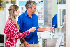 Shop assistant in hardware store counseling customer about lavat Royalty Free Stock Images