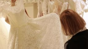 Shop assistant helping for beautiful young woman choosing a wedding dress in a wedding shop. Shop assistant helping for pretty young bride choosing a wedding stock video