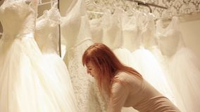 Shop assistant helping for beautiful young woman choosing a wedding dress in a wedding shop. Shop assistant helping for pretty young bride choosing a wedding stock video footage