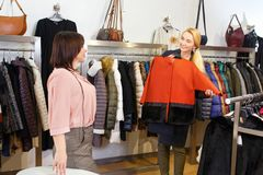 Shop assistant helping chooses clothes. Sales consultant helping chooses clothes for the customer in the store. Shopping with stylist. Beautiful female shop Stock Images