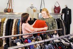 Shop assistant helping chooses clothes. Sales consultant helping chooses clothes for the customer in the store. Shopping with stylist. Beautiful female shop Stock Photo