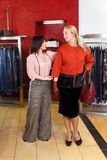 Shop assistant helping chooses clothes. Sales consultant helping chooses clothes for the customer in the store. Shopping with stylist. Beautiful female shop Royalty Free Stock Photo