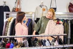 Shop assistant helping chooses clothes. Sales consultant helping chooses clothes for the customer in the store. Shopping with stylist. Female shop assistant Royalty Free Stock Photos