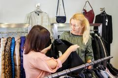Shop assistant helping chooses clothes. Sales consultant helping chooses clothes for the customer in the store. Shopping with stylist. Female shop assistant Stock Photo