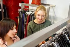 Shop assistant helping chooses clothes. Sales consultant helping chooses clothes for the customer in the store. Shopping with stylist. Beautiful female shop Royalty Free Stock Photos