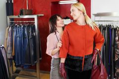 Shop assistant helping chooses clothes. Sales consultant helping chooses clothes for the customer in the store. Shopping with stylist. Female shop assistant Stock Photography