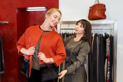 Shop assistant helping chooses clothes. Sales consultant helping chooses clothes for the customer in the store. Shopping with stylist. Female shop assistant Royalty Free Stock Images