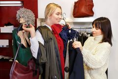 Shop assistant helping chooses clothes. Sales consultant helping chooses clothes for the customer in the store. Shopping with stylist. Female shop assistant Royalty Free Stock Image