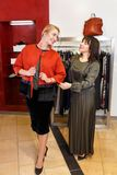 Shop assistant helping chooses clothes. Sales consultant helping chooses clothes for the customer in the store. Shopping with stylist. Female shop assistant Royalty Free Stock Photo