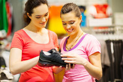Shop assistant helping customer. Choosing sports shoes Royalty Free Stock Photography