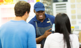Shop assistant helping customer. Friendly african shop assistant helping couple choose paint color at hardware store Royalty Free Stock Photos