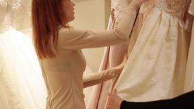 Shop assistant helping for pretty young woman choosing a wedding dress in a wedding shop stock video footage