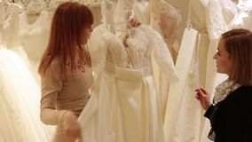 Shop assistant helping for pretty young woman choosing a wedding dress in a wedding shop stock footage