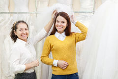 Shop assistant  helps the bride in choosing bridal veil Royalty Free Stock Image