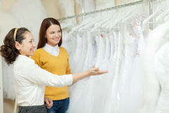 Shop assistant  helps bride in choosing  dress Royalty Free Stock Images