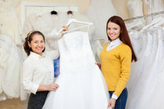 Shop assistant  helps the bride in choosing  dress Stock Image