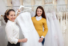 Shop assistant  helps the bride in choosing  dress Stock Photography
