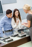 Shop assistant helps couple to select jewelry. At jeweler's shop. Concept of wealth and luxurious life Royalty Free Stock Photos