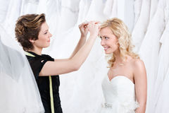 Shop assistant helps to fix the wedding tiara. White background stock image